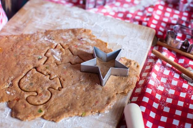 クリスマスと新年のためにジンジャーブレッドのクッキー生地を切る