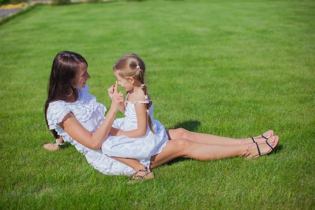 Маленькая девочка и ее молодая мать веселятся во дворе
