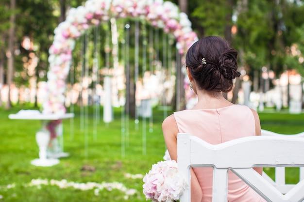 屋外式で長いドレスを着た美しい若い女性の背面図