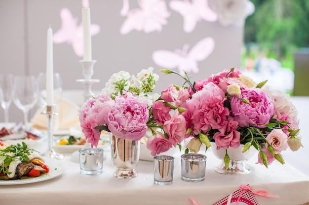 Красивый яркий букет пионов на свадебном столе в вазе