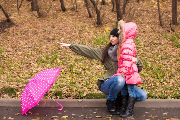 Маленькая девочка и ее мать гуляют с зонтиком в дождливый день