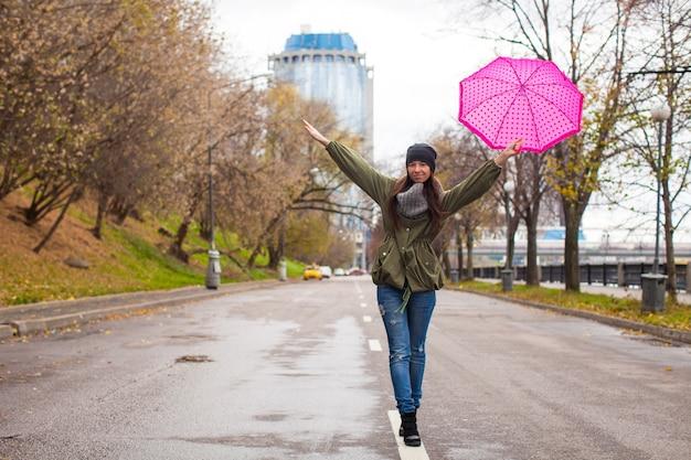 秋の雨の日に傘で歩く若い女性