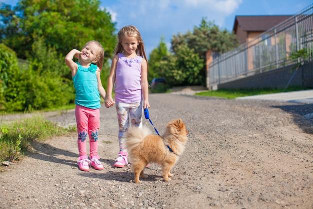 Две маленькие девочки гуляют с маленькой собачкой на поводке на улице