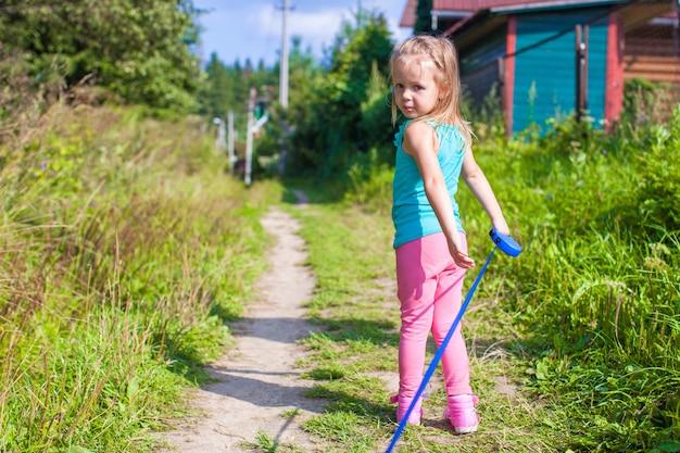 ひもにつないで犬と歩いている少女