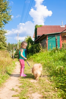 Маленькая девочка гуляет со своей собакой на поводке