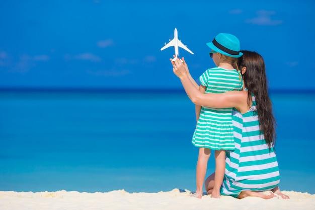 小さな女の子とビーチで飛行機の白いミニチュアとママ