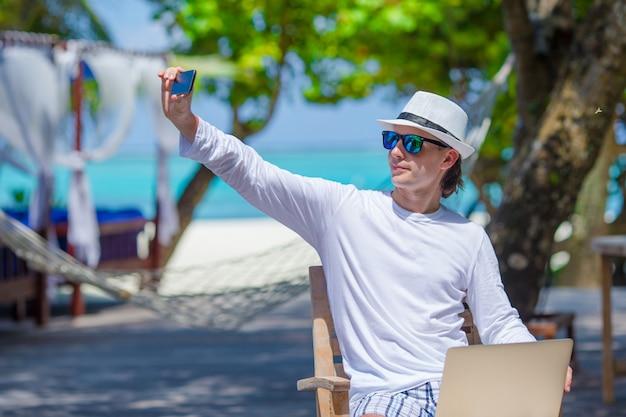 若い男は、熱帯のビーチで携帯電話で写真を作る