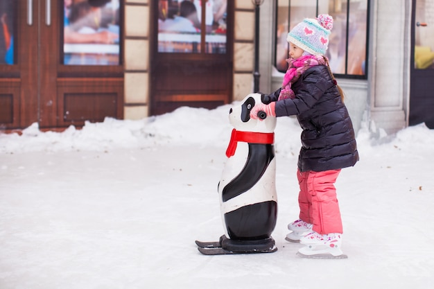 アイススケートリンクでスケートを楽しむ愛らしい幸せな女の子