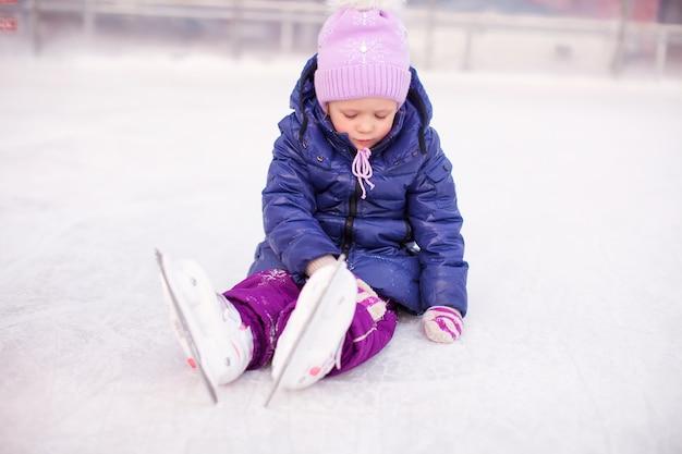 秋の後スケートリンクに座っている悲しい少女