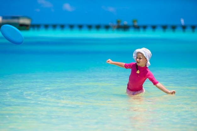 愛らしい幸せな少女は、ビーチでの休暇に浅い水で楽しい時を過す