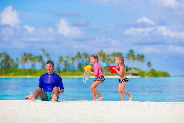 かわいい小さな女の子と父親の夏休みにビーチおもちゃを楽しんで
