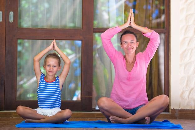 Молодая женщина и маленькая девочка занимаются фитнесом на открытом воздухе на террасе