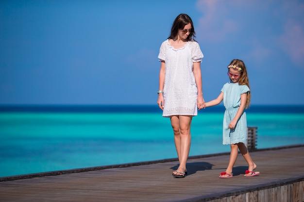 エキゾチックなリゾートで木製の桟橋の上を歩く少女と若い母親