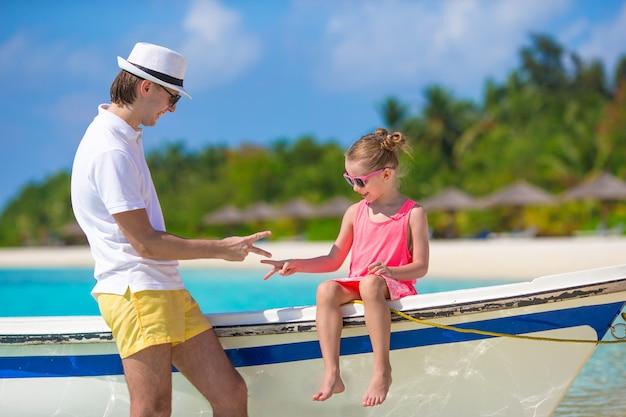 小さな女の子と熱帯のビーチでの休暇中にボートの父