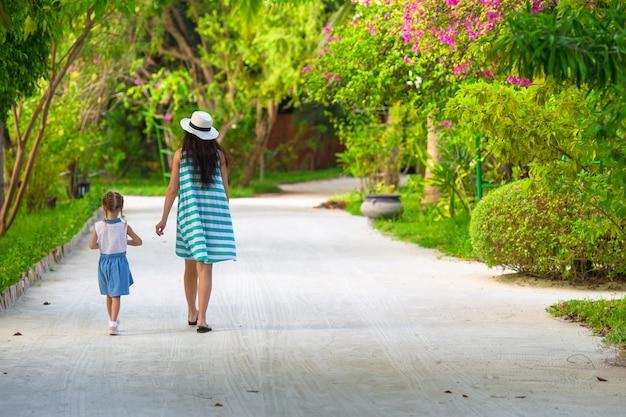 ビーチでの休暇中に小さな女の子と若い母親
