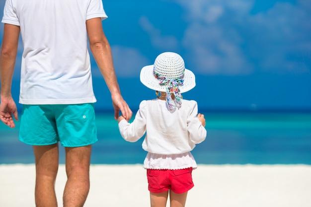 熱帯のビーチでの休暇中に愛らしい少女と幸せな父