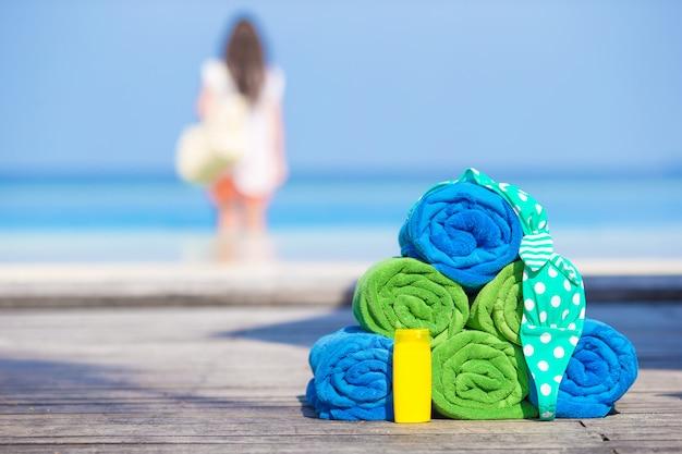 ビーチと夏のアクセサリーのコンセプト - カラフルなタオル、水着と日焼け止め