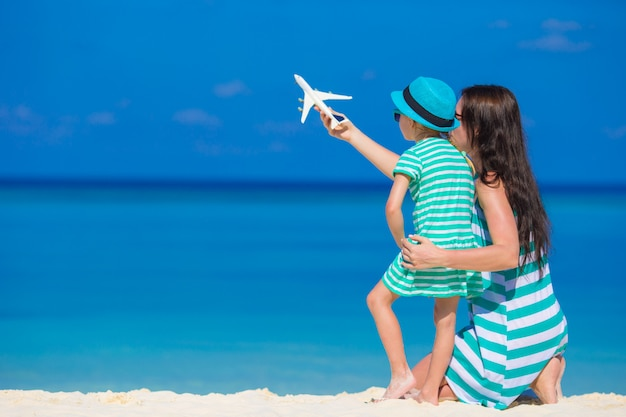 Молодая женщина и маленькая девочка с миниатюрой самолета на пляже