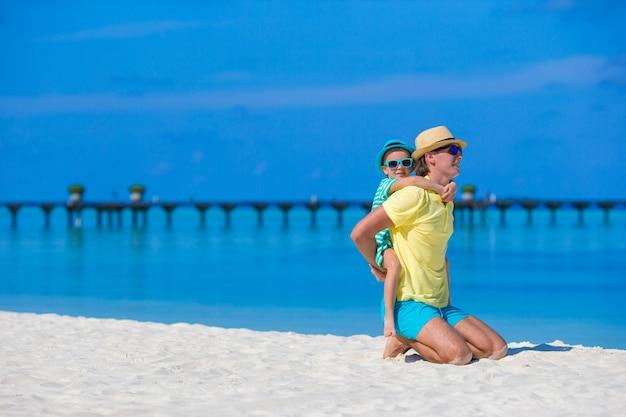 熱帯のビーチでの休暇中に小さな女の子と若い父