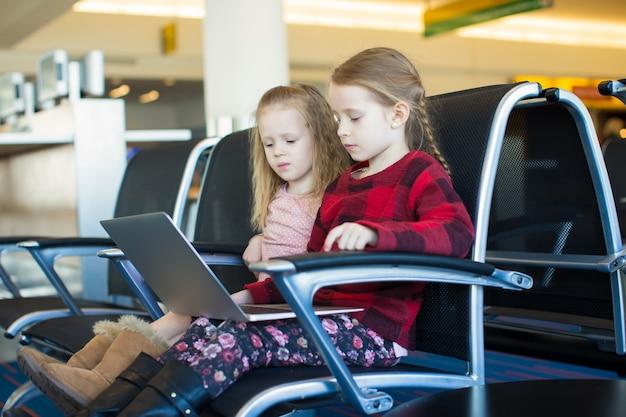 彼の飛行を待っている間に空港でラップトップを持つ子供