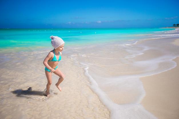 エキゾチックなビーチで浅い水の中を実行しているかわいい幼児の女の子