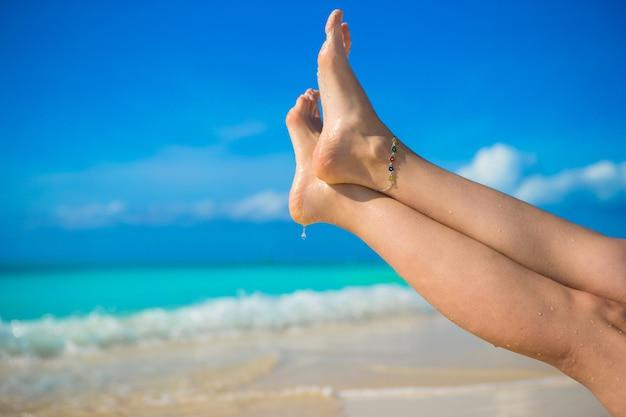 白い砂浜のビーチで女性の足のクローズアップ