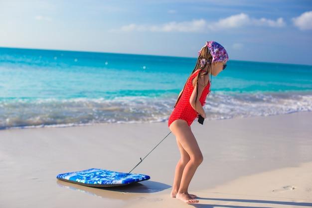 愛らしい少女は白い海岸でサーフボードを引っ張る