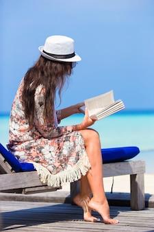 Молодая женщина читала книгу во время пляжного отдыха