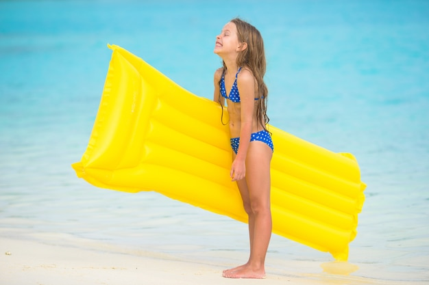 白いビーチで膨脹可能な空気マットレスで愛らしい幸せな女の子