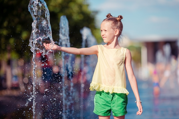 愛らしい少女は暑い晴れた日に通りの噴水で楽しい時を過す