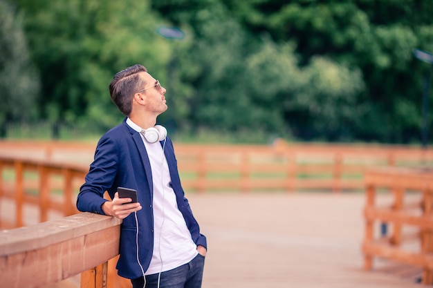 ヨーロッパの都市の屋外でコーヒーを飲んで幸せな若い都市男