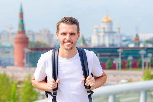 若い男が幸せな肖像画の笑みを浮かべてハイキングします。街を歩いて男性ハイカー
