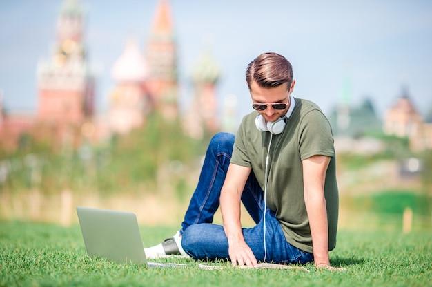 幸せな都市の若い男は、街で彼の休憩を楽しむ