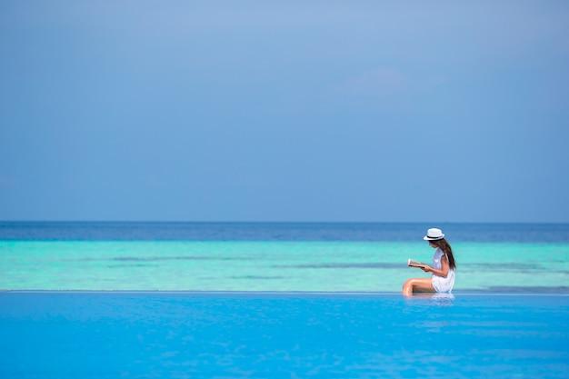 Молодая девушка читает книгу возле бассейна