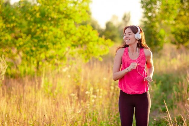 屋外のスポーティな演習を行う若い笑顔の女性