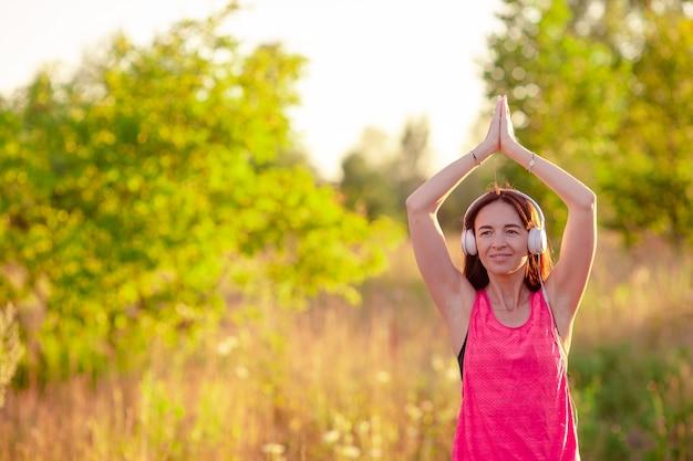 Молодая усмехаясь женщина делая спортивные упражнения на открытом воздухе