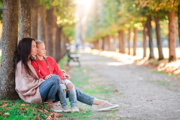 母と秋の日に公園で屋外の小さな子供の家族