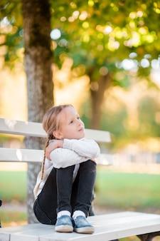 美しい秋の日の屋外でのかわいい女の子。秋のベンチに小さな女の子
