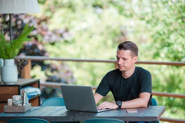 コーヒーを飲みながらの屋外カフェでラップトップを持つ若者。モバイルスマートフォンを使用している人。