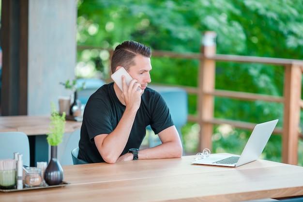 コーヒーを飲みながら屋外カフェでスマートフォンで話している若い男。モバイルスマートフォンを使用している人。