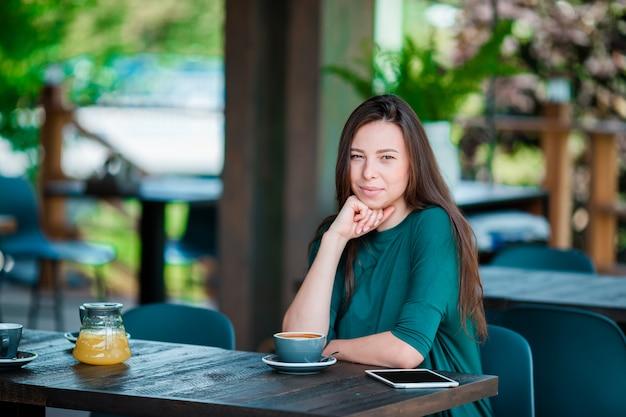 屋外カフェで朝食を持っている美しい女性。コーヒーを飲みながら幸せな若い都市女性
