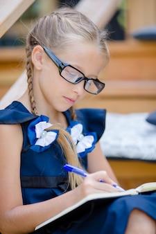 ノートと鉛筆を屋外で愛らしい小さな学校の女の子。学校に戻る。