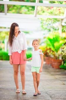 小さな女の子と夏休みに高級リゾートを歩いて母