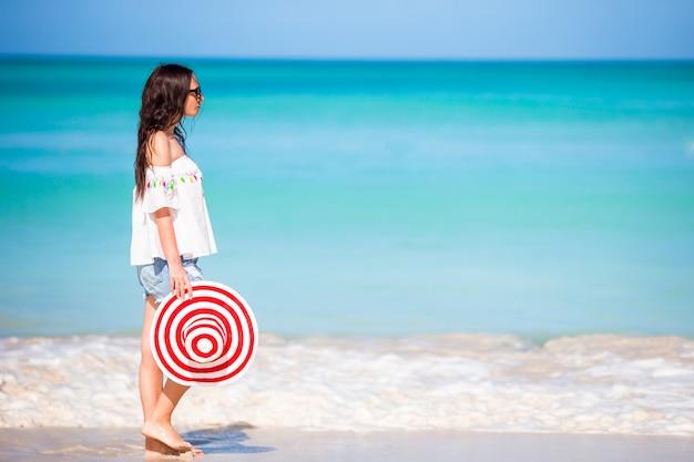 白い熱帯のビーチの若い美しい女性。海岸に大きな赤い帽子と白人の女の子
