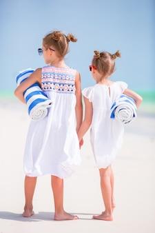 白い熱帯のビーチでビーチタオルで愛らしい女の子