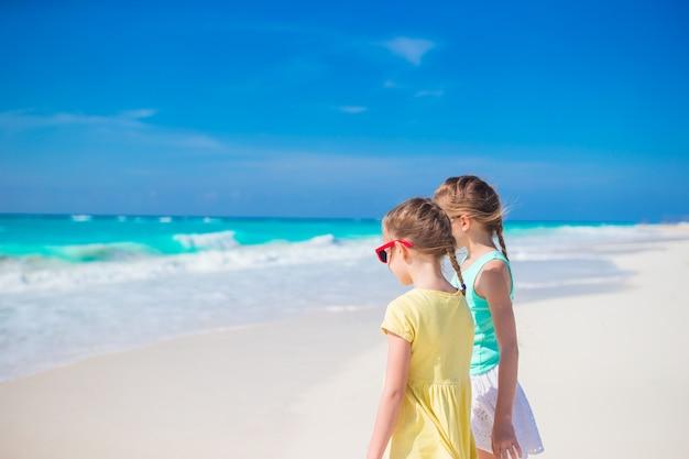 Маленькие девочки веселятся на тропическом пляже, играя вместе на берегу моря