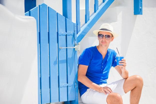ギリシャの通り屋外でコーヒーを飲む男性。屋外カフェでホットコーヒーの少年