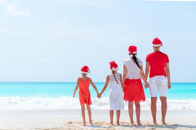 クリスマス休暇を祝う熱帯のビーチに赤いサンタ帽子で幸せな家族