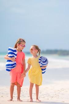 熱帯のビーチで海で泳ぐ準備ができてタオルを持つ少女