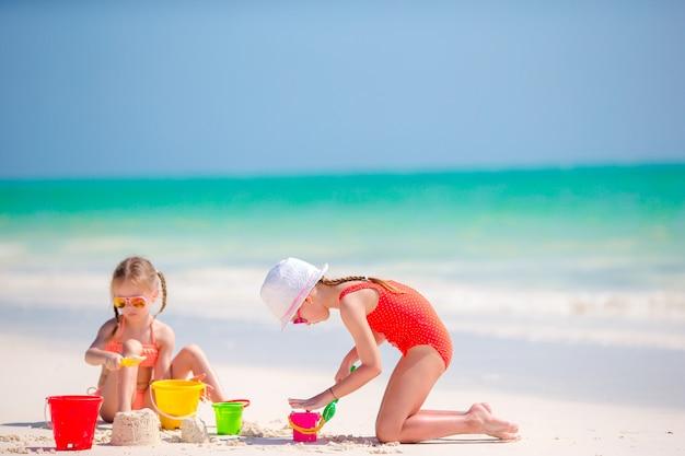 夏休みの間に愛らしい女の子。白いビーチでビーチおもちゃで遊ぶ子供たち